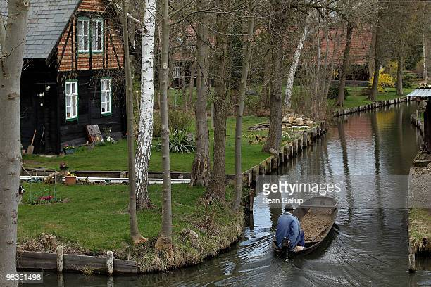 A local resident in a pirogue navigates the narrow canals of the Spreewald forest on April 9 2010 in Luebbenau Germany The Spreewald is interlaced...