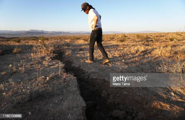 A local resident inspects a fissure in the earth after a 64 magnitude earthquake struck the area on July 4 2019 near Ridgecrest California The...
