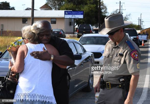Local resident Jamie Rose is hugged by church member Raymond Antonio as she delivers flowers at the entrance to the First Baptist Church after a mass...