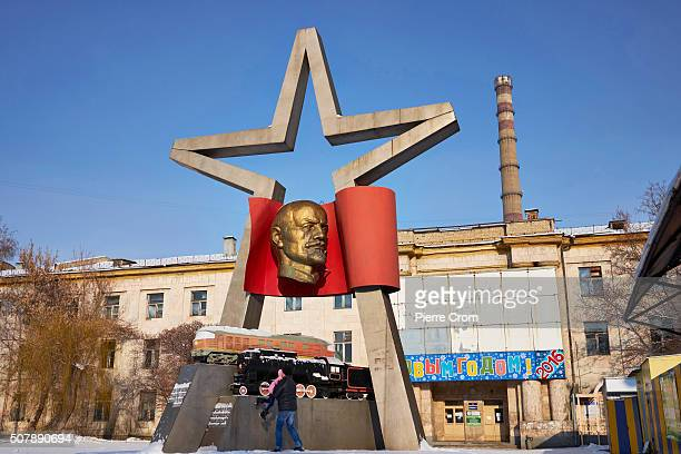 Local resident lifts his daughter from a monument likening Lenin outside the train factory on January 1, 2016 in Luhansk. Over 800 Lenin monuments...
