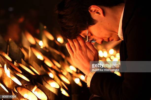 A local resident lights candles and prays for victims of the Great Hanshin earthquake during a memorial ceremony on January 17 2016 in Kobe Japan...