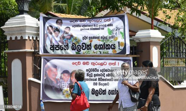 A local resident looks at banners put up in honour of victims of the St Sebastian's Church suicide bomb attack in Negombo on April 24 2019 The...