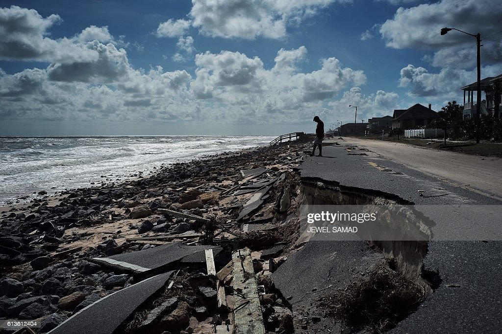 TOPSHOT - A local resident looks at debris and part of closed A1A highway, washed out by Hurricane Matthew in Flagler Beach, Florida, on October 9, 2016. A weakened Hurricane Matthew made landfall October 8 in South Carolina, nearing the end of a four-day rampage that left a trail of death and destruction across the Caribbean and up the southeastern US coast. In Haiti, where Matthew was a monster Category 4 when it slammed into the poorest country in the western hemisphere Tuesday, the official death toll rose to at least 336. Nine were killed in the United States. / AFP / Jewel SAMAD