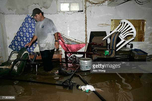Local resident Mario Rivela walks in flood water as he checks the damage of his house's basement June 26 2006 in the Huntington area of Alexandria...