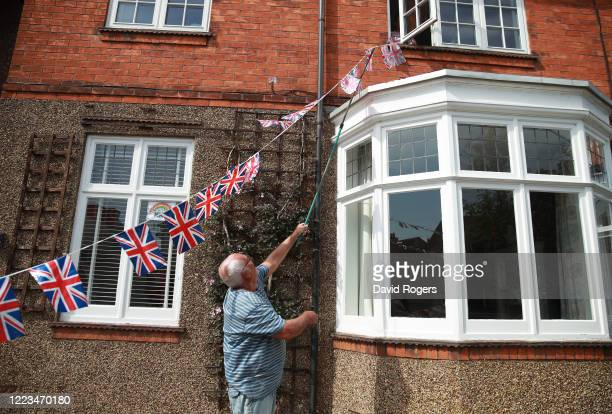 Local resident Mick Jackson decorates his house with VE Day bunting on May 07, 2020 in Northampton, United Kingdom. The UK will commemorate the 75th...