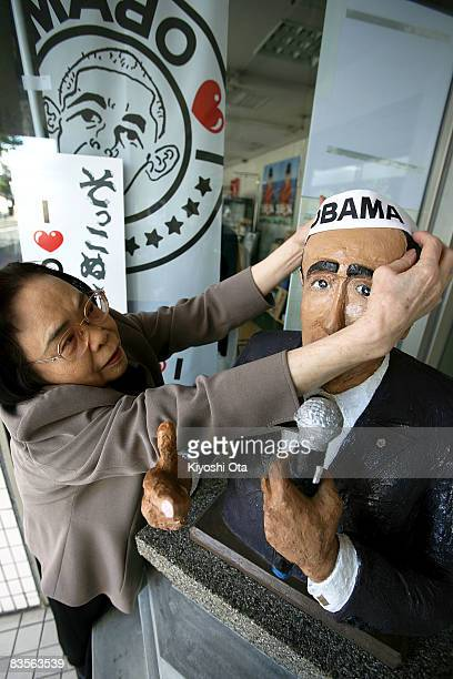 Local resident Misao Miura adjusts a headband on a statue of the Democratic presidential candidate US Sen Barack Obama displayed in front of a...
