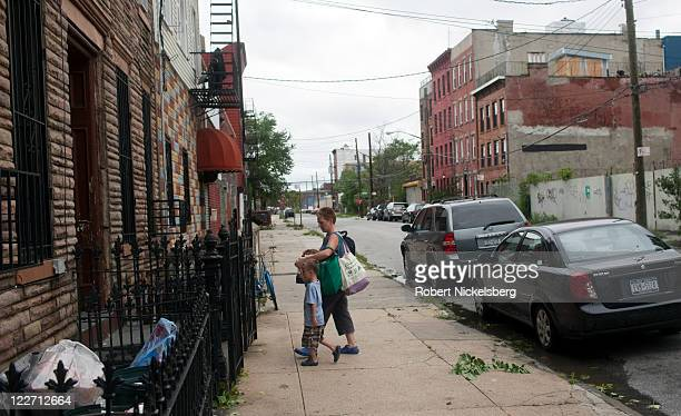 A local resident of Red Hook Shannon Hummel walks with Henry McFadden after returning to their apartment August 28 2011 in the Brooklyn borough of...