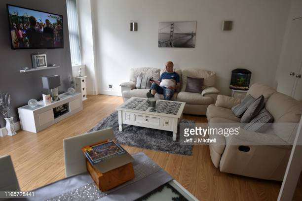 Local resident on Clune Park estate Ramsay Stewart relaxes inside his home on August 2 2019 in Port Glasgow Scotland Formerly the home to shipyard...