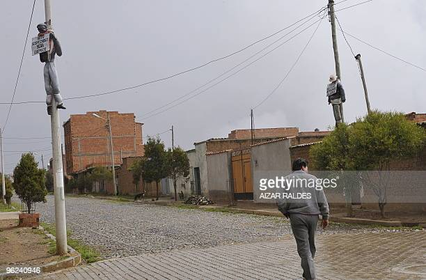 A local resident passes by dummies hanged from lamp posts with placards that warn possible burglars that they shall be lynched if caught January 14...