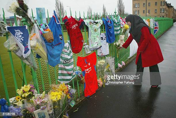 Local resident places flowers amongst the tributes that mark the scene, March 18, 2004 where 15-year-old Kriss Donald was abducted by a gang of five...