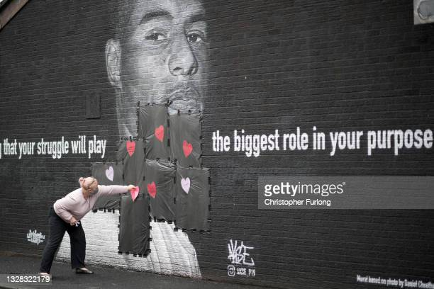 Local resident puts love hearts and slogans on the plastic that covers offensive graffiti on the vandalised mural of Manchester United striker and...