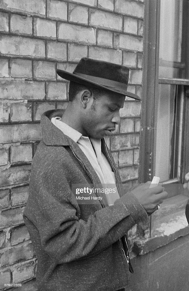 Local resident Raymond Mawson inspects damage on the street in the aftermath of the Notting Hill race riots, London, 1st September 1958.
