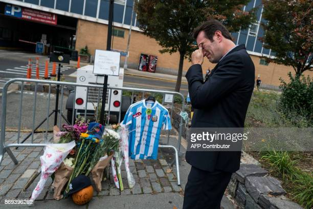 TOPSHOT A local resident reacts after placing an Argentinian soccer jersey at a makeshift memorial for the October 31 terror attack victims along a...