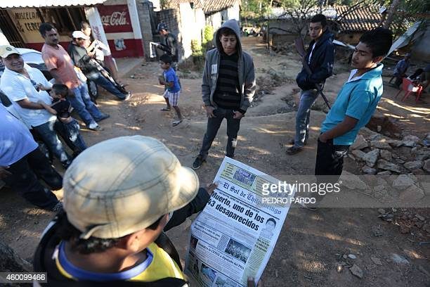 A local resident reads a newspaper with news about the identification of Alexander Mora one of the 43 missing students whose remains where found in a...