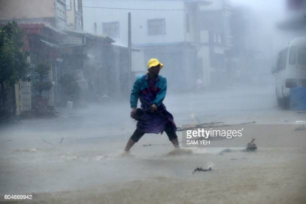 TOPSHOT A local resident removes a rock from a blocked road in southern Pingtung county as typhoon Meranti slash southern Taiwan on September 14 2016...