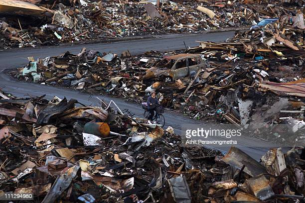 A local resident rides a bicycle among debris on March 31 2011 in Kesennuma Miyagi Prefecture JapanThe 90 magnitude strong earthquake struck offshore...