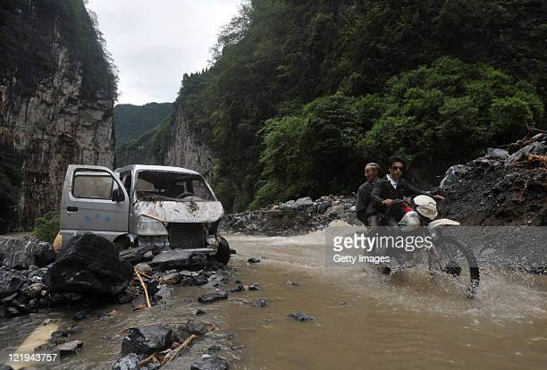 A local resident rides along a flooded road after mudslide on August 23 2011 in Xingshan County Hubei Province of China One confirmed dead one...