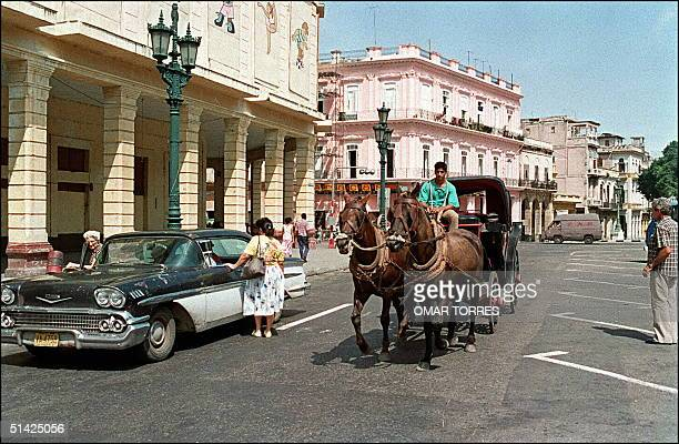 A local resident riding a horsedrawn carrigba passes by a classic 'oldtimer' US made Chevrolet 26 September 1991 on one of the main Havana'streets