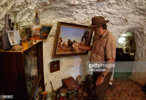 Local resident Ross Jones cleans a painting in his dugout home near the outback town of White Cliffs on October 23 2002 in New South Wales Australia...