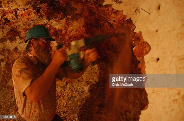 Local resident Ross Jones excavates a new room in his dugout home in the outback town of White Cliffs on October 23 2002 in New South Wales Australia...