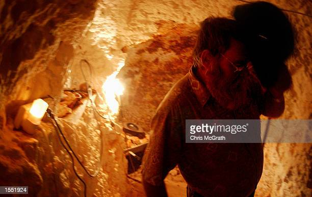 Local resident Ross Jones excavates a new room in his dugout home near the outback town of White Cliffs on October 23 2002 in New South Wales...