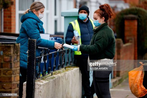 Local resident seals their completed coronavirus test kit after a volunteer to collected it from their step, as part of surge testing for the South...