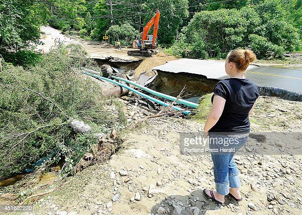 Local resident Sophie Post looks at her former garden and large fir tree that has tumbled into the washed out gorge made by the flood waters as MDOT...