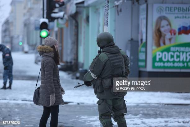 A local resident speaks to an armed man in military fatigues blocking access to government buildings in eastern Ukraine's rebelheld Lugansk on...