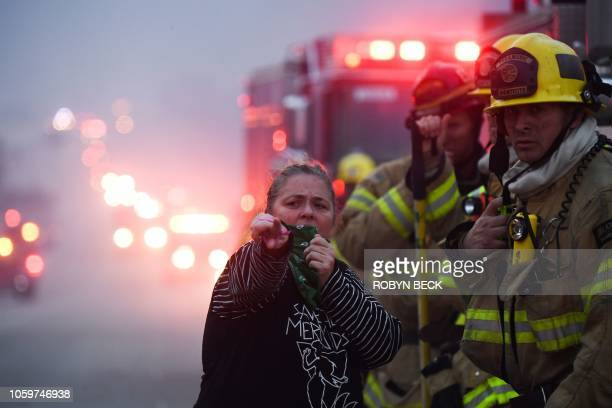 A local resident speaks with firefighters stationed along Pacific Coast Highway to battle the Woolsey Fire on November 9 2018 in Malibu California...