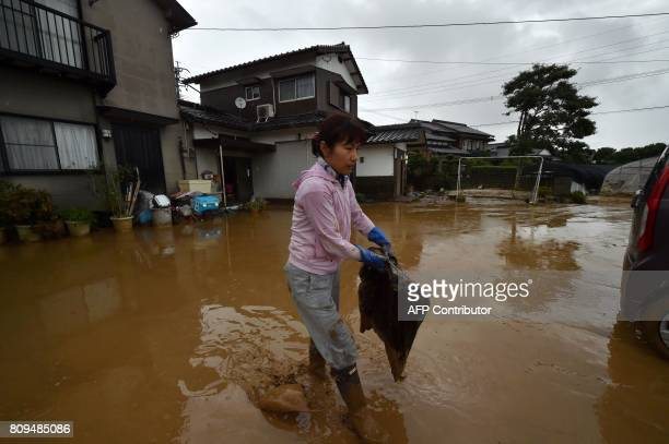 A local resident takes out flooddamaged belongings from her house in Asakura Fukuoka prefecture on July 6 2017 One person reportedly died and at...