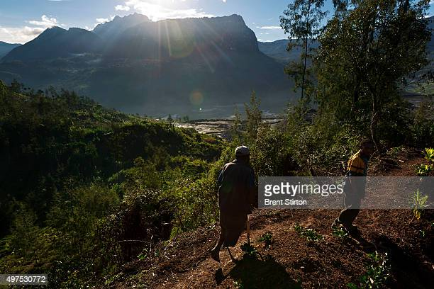 Local resident Thomas Petale and his wife work in their vegetable garden overlooking the processed ore dumps of the Porgera Joint Venture Mine Papua...