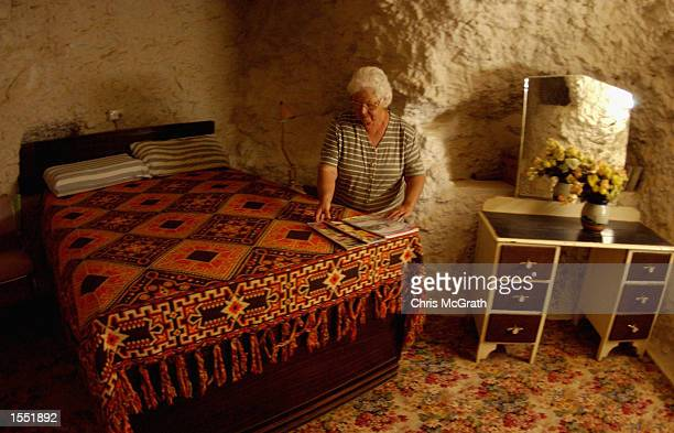 A local resident tidies up in the bedroom of a dugout home in the outback town of White Cliffs on October 23 2002 in New South Wales Australia In...