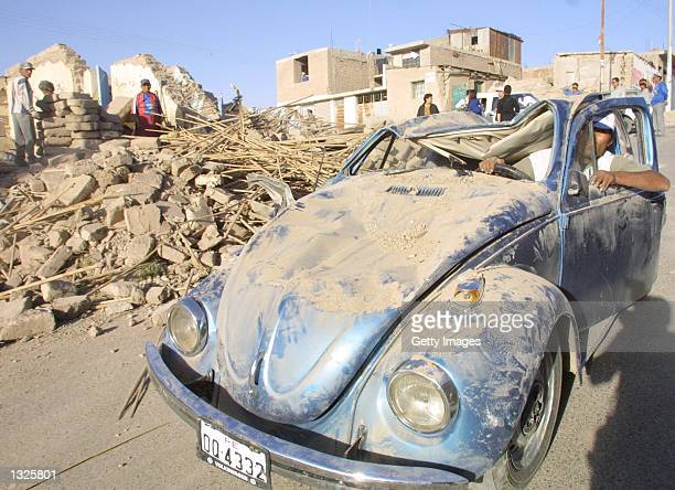 A local resident tries to get his car started June 24 2001 after it was damaged during an earthquake in the town of Moquegua south of Arequipa Peru...