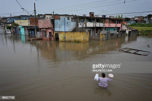 A local resident wades through a flooded street bringing back home some bread and milk at Jardim Izildinha neighborhood a flooded area on the edge of...