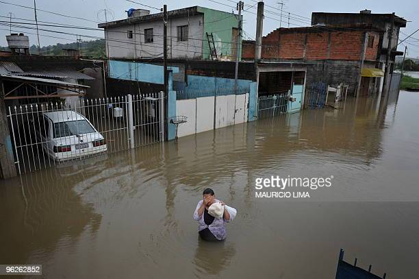 A local resident wades through a flooded street carrying bread and milk at Jardim Izildinha neighborhood a flooded area on the edge of the northern...