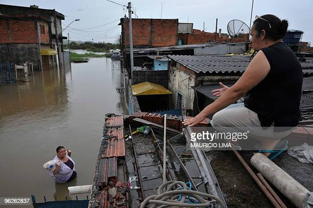 A local resident wades through a flooded street to bring back home some bread and milk at Jardim Izildinha neighborhood a flooded area on the edge of...