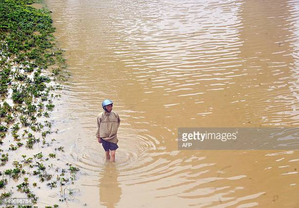 A local resident wades through flood waters on a road in New Taipei City on August 2 2012 Typhoon Saola pounded Taiwan with fierce winds and...