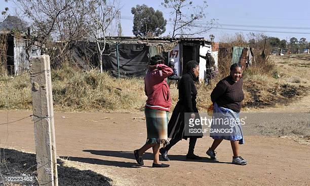 Local resident walk down a road in the township of Sharpeville south of Johannesburg on June 19 2010 AFP PHOTO / ISSOUF SANOGO