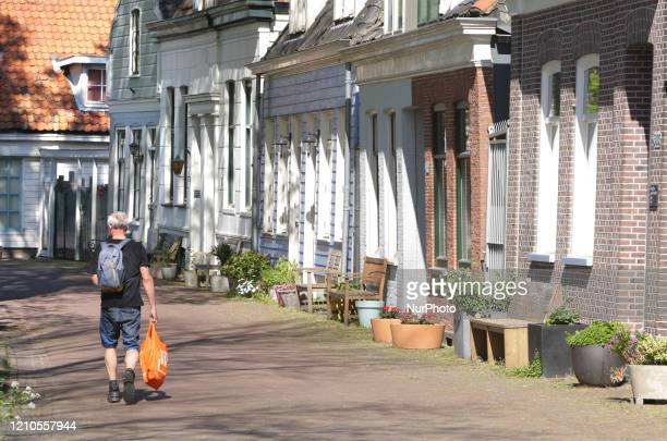 A local resident walking on empty Nieuwendammerdijk street with old antique houses from 1609 on April 20 2020 in AmsterdamNetherlands Dutch Prime...