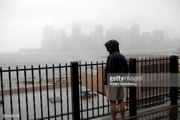A local resident walks along the Promenade in Brooklyn Heights overlooking the East River park as the eye of the storm passes over the region August...