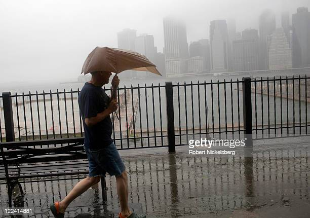 A local resident walks along the Promenade in Brooklyn Heights with a view of the Manhattan skyline as the eye of the storm passes over the region...