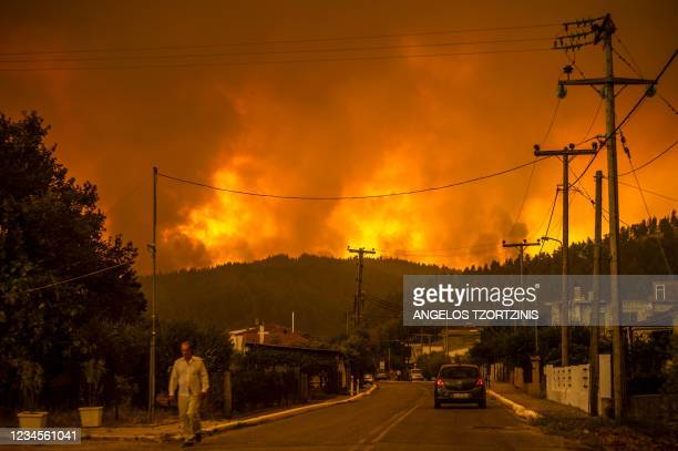 Local resident walks as a wildfire rages near the village of Gouves, on Euboea island, second largest Greek island, on August 8, 2021. - Hundreds of...