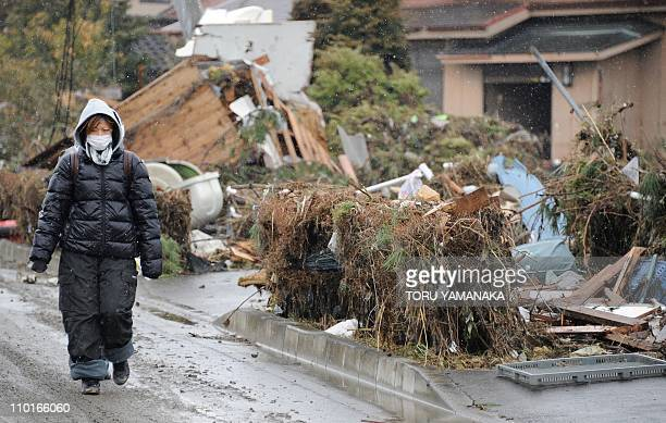 A local resident walks beside collapsed houses and debris left by the March 11 tsunami and earthquake in Natori in Miyagi Prefecture on March 16 2011...