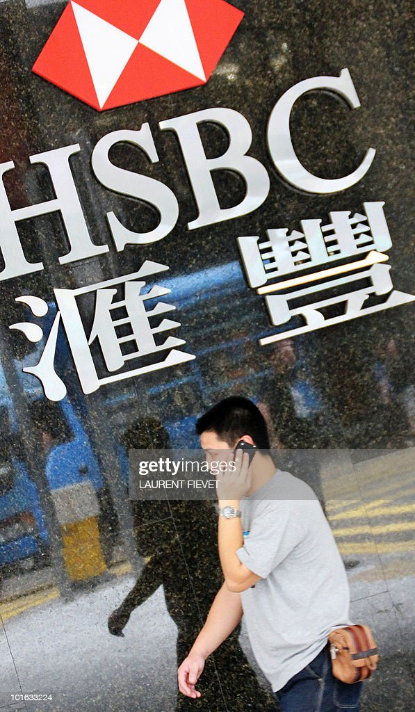 A local resident walks in front of the Hong Kong and Shanghai Banking Corporation (HSBC) logo in Hong Kong on June 5, 2010. HSBC has become the latest bank to respond to regulatory pressure to spin off its private equity activities by starting talks about management buy-outs at five of its private equity businesses overseeing 8.8 billion USD of assets.