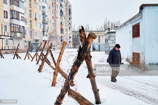 A local resident walks past a barbed wire fence in the frontline city of Avdiivka as Ukrainian forces pushed back an attack by proRussian rebels on...