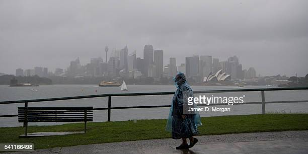 A local resident walks to the ferry at Cremorne Point in pouring rain on June 19 2016 in Sydney Australia Flood warnings have been issued for the...