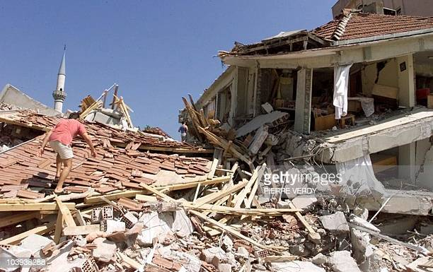 Local resident walks up on a collapsed roof among piles of rubble in the suburbs of Izmit some 100 kilometers East of Istanbul 18 August 1999...