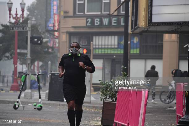 Local resident wears a respirator as he jogs in downtown Portland, Oregon where air quality due to smoke from wildfires was measured to be amongst...
