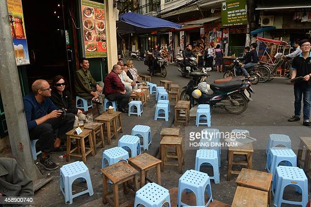 Local residents and foreign tourists enjoy food and drinks at small openair restaurants in the ancient quarter of Hanoi on November 13 2014 The...