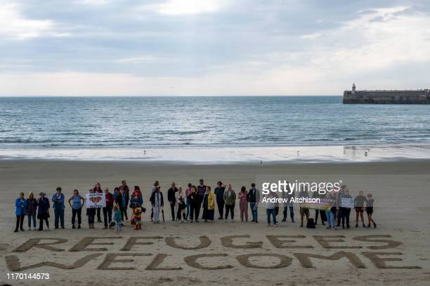 Local residents and members of an Kents Anti-Racism Network peacefully stand behind Refugees Welcome written in the sand on Sunny Sands Beach,...